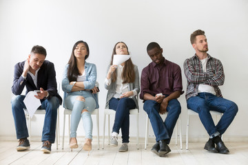 Diverse casual work candidates get bored while sitting in queue for job interview, multiethnic applicants holding smartphones, tablets and resumes tired of waiting. Concept of hiring, employment, HR