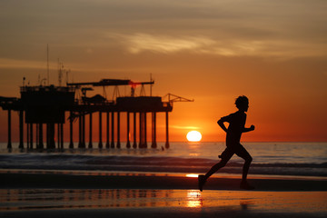 Silhouette of runner at sunset on La Jolla Shores Beach near Scripps Institute of Oceanography Pier, San Diego, California, USA