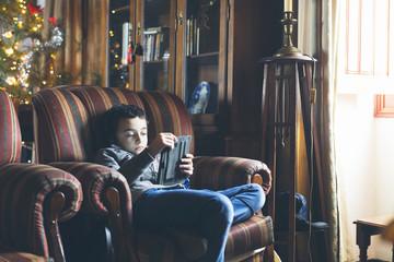 Boy in headphones using tablet in armchair at home