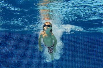 Smiling boy swimming underwater in pool