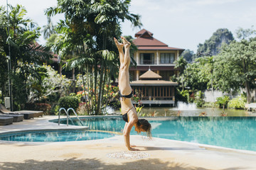 Young woman in bikini doing handstand beside outdoor swimming pool, Tambon Ao Nang, Chang Wat Krabi, Thailand