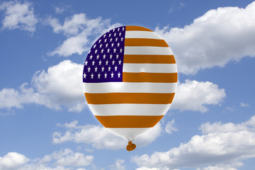 Inflatable balloon with USA flag in blue sky and clouds