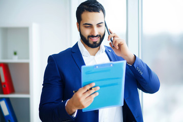 Office Business Man in a Light Office with Big Windows Holding a Blue Folder in Hand. Man Dressed in Blue Costume and White Shirt. High Resolution