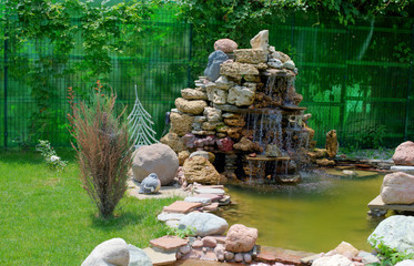 little artificial pond with fountain on the edge and water lilies. Landscape design.