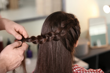 Professional hairdresser working with client in beauty salon, closeup