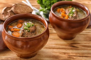 Crock pots with stewed meat on table