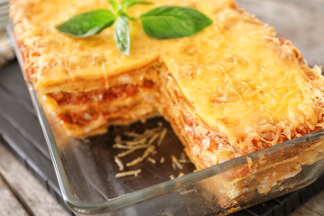Tasty lasagna in baking dish on table