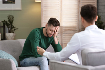 Male psychologist with client in office