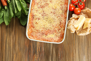 Composition with tasty spinach lasagna, cheese and vegetables on wooden background