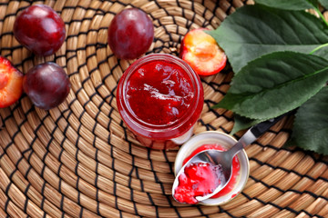 Glass jar with delicious homemade plum jam on wicker mat
