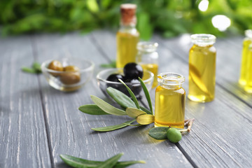 Composition of olives in bowl and bottles with oil on wooden table