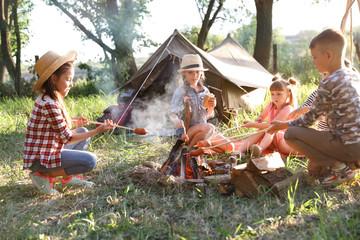 Little children frying sausages on bonfire. Summer camp
