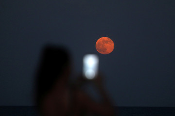 A woman takes a picture of the moon, typically called a 'Strawberry Moon' when full in June, in Larnaca