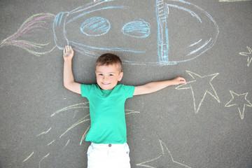 Little child lying near chalk drawing of rocket on asphalt, top view