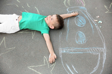 Little child lying near chalk drawing of rocket on asphalt