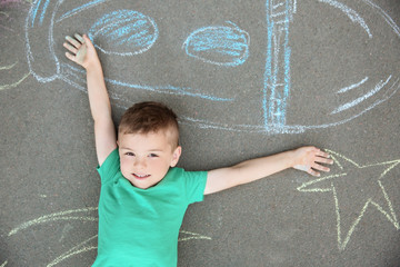 Little child lying near chalk drawing of rocket on asphalt, top view