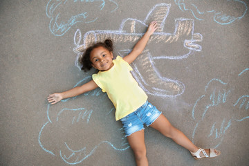 Little African-American child lying near chalk drawing of airplane on asphalt, top view