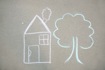 Child's chalk drawing of house and tree on asphalt, top view