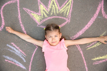 Little child lying near chalk drawing of wings and crown on asphalt, top view