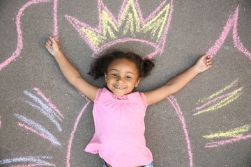 Little African-American child lying near chalk drawing of wings and crown on asphalt, top view