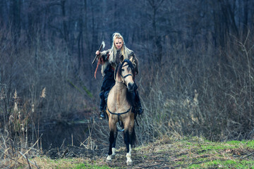 Scandinavian northern viking riding horse with ax in hand. Northern warrior woman riding in forest in war clothes with fur collar, war makeup.