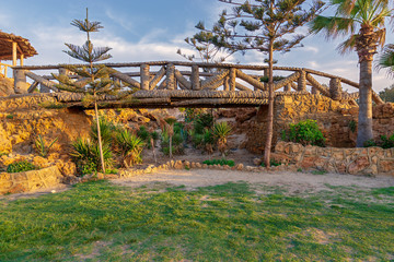 Wooden bridge made of palm trunks over a cavity full of bushes at Montaza park in summer time, Alexandria, Egypt
