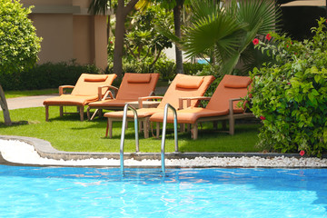Sunbeds near modern swimming pool at resort