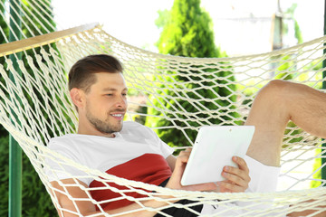 Man with tablet relaxing in hammock outdoors on warm summer day