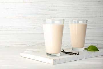 Glasses with vanilla milk shakes on table