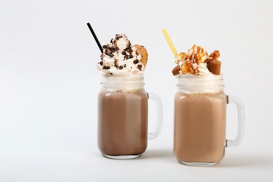 Mason jars with delicious milk shakes on white background