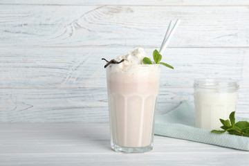 Glassware with delicious milk shakes on table
