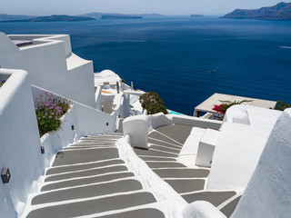Steps and white architecture on Santorini island, Greece. Beautiful summer landscape, sea view.