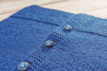 blue knitted sweater with marble buttons, close-up