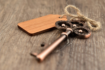 Decorative metal key on a wooden background stock images. Decorated key images. Romantic key with wooden label. Key on the table