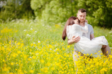 Wall Murals Couple walking in the yellow meadow, man keeping a woman in his arms