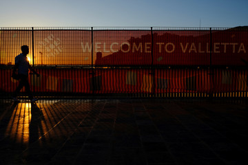 A man walks past a Valletta 2018 European Capital of Culture banner on the pedestrian bridge leading in and out of Valletta