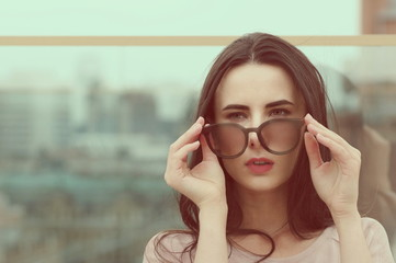 A long-haired young brunette woman plays with sunglasses