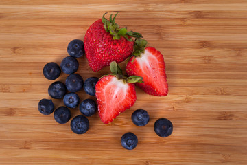 Overview whole blue berries and sliced Strawberries on bamboo cutting board