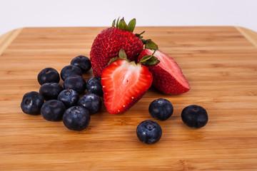 Strawberries blue berries on light wood bamboo cutting board