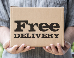 "Free delivery concept: a parcel brought by hand with ""free delivery"" text"