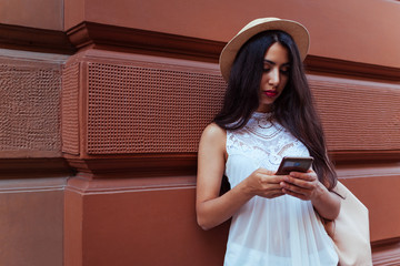 Beautiful tourist girl using smart phone outdoors. Middle-eastern woman searching for right way with navigator