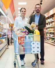 Happy couple is standing with cart with products
