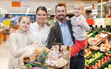 Smiling family with their children standing together in the shop