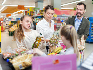 Family is standing with food near cashbox in supermarket