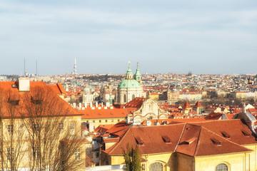 View of Prague: Vrtbovska Garden, Saint Nicholas Church, tiled roofs on blue sky background