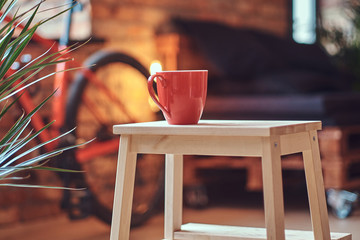 Minimalism concept. Close-up image of a red cup on a wooden stool on a room with a loft interior.