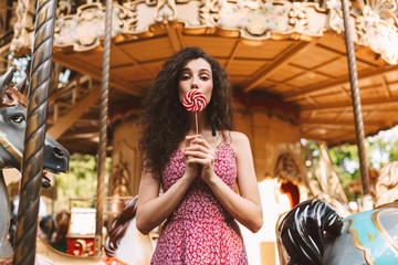 Photo sur Plexiglas Attraction parc Beautiful lady with dark curly hair in dress standing and covering her mouth with candy while dreamily looking in camera with carousel on background