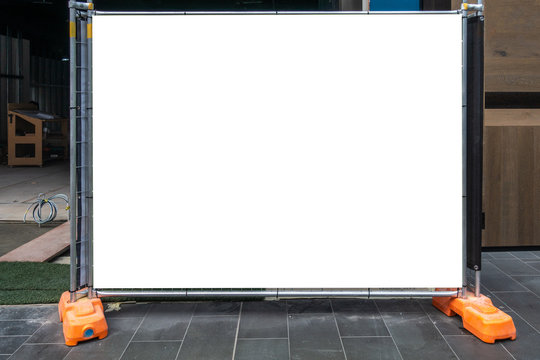 Rectangle blank advertising space on construction barrier/fence. White mock up template of temporary fencing outside renovation site.