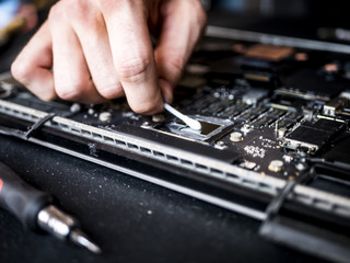 hand with wedding tampone clearing the broken laptop and repairing mother board