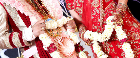 The bride and groom at the Indian wedding garlands or Jaimala ceremony